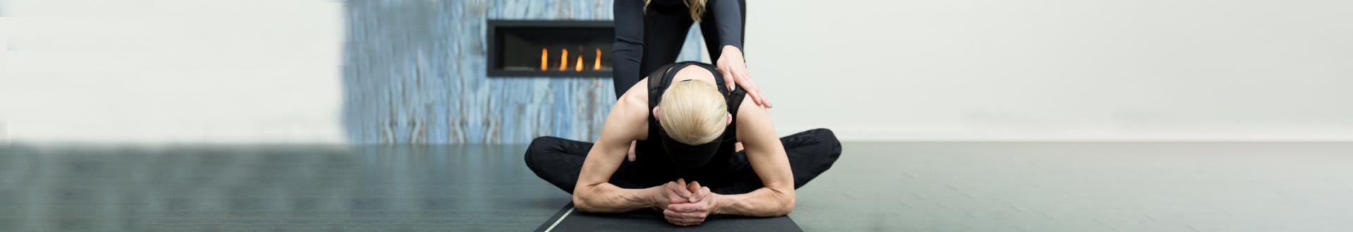 woman guiding a person doing yoga